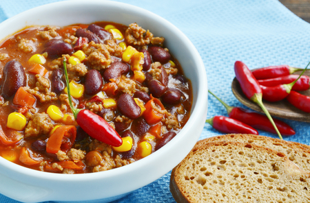 chili con carne on white bowl and Black bread or Rye bread