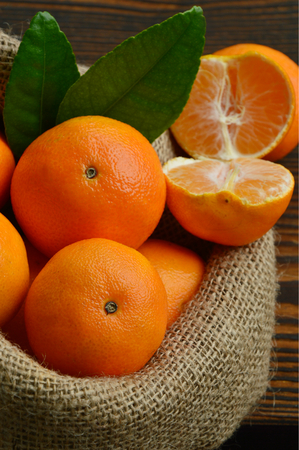 clementines: A lot of Clementines, orange or citrus in sack bag on wooden background. Stock Photo