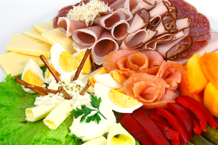 Various mixed meat and vegetable appetizers on white background. Stock Photo