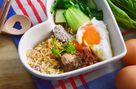 Instant noodle with egg, minced pork, bok choy in heart shape bowl.
