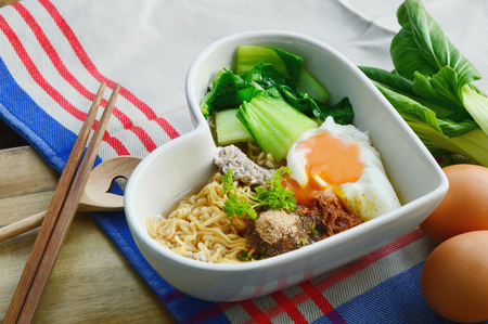 bok choy: Instant noodle with egg, minced pork, bok choy in heart shape bowl.