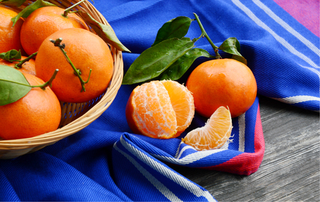 A lot of Clementines, orange or citrus with blue cloth on wooden background.