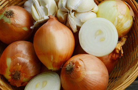 Mixed onions and garlic in basket on wooden background.