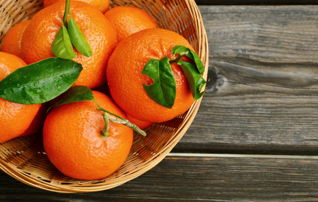 clementines: A lot of Clementines, orange or citrus with leaves in basket on wooden background. Stock Photo