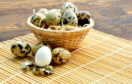 Quail eggs in basket with straw on wooden background