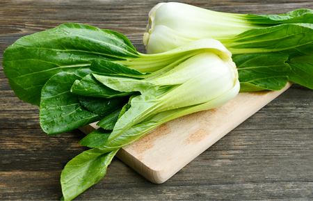 Organic bok choi or choy with water drop on wooden broad and wooden floor Stock Photo