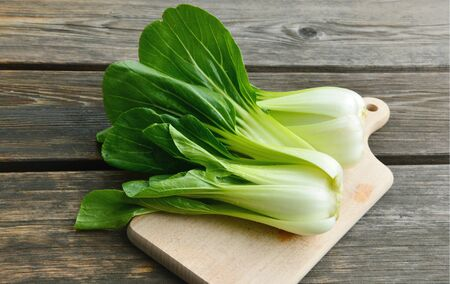 Bok choy or Chinese cabbage on wooden board and wooden floor 스톡 콘텐츠