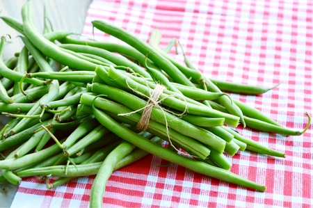 Green beans tied with rope on wooden background Stock Photo