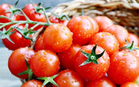 fresh cherry tomatoes in basket with water drop on wooden background Stock Photo