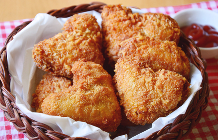 Fried chicken wings are heart-shaped in a basket with ketchup