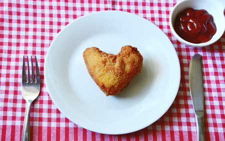 Fried chicken wings are heart-shaped in the dish with ketchup