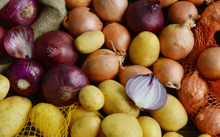 Many potatoes, red and yellow onions put together in the floor