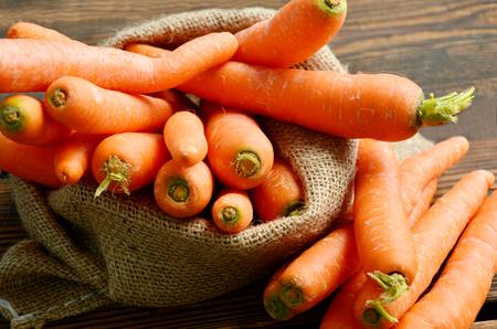 Carrots in sack bag on wooden floor