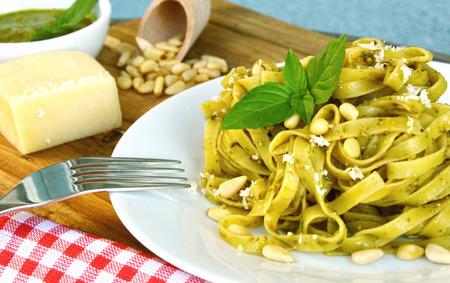 Basil pesto pasta on wooden background