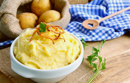 Mashed potatoes or puree in white bowl with crisp onions and parsley on wooden background