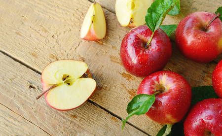 Red apples or gala apples with fresh leaves and water drops on wooden background