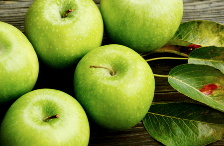 Green apples on leaf on wooden background