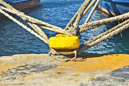 yellow mooring bollard with rope in the ship port