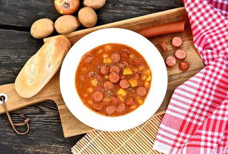 Potato goulash with Debreziner sausage or German name is Kartoffelgulasch mit Debreziner on wooden background