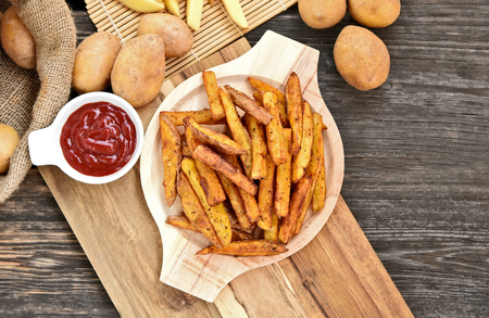 Homemade Crispy Seasoned French Fries.French fries with spicy seasoning in wooden plate on wooden broad.