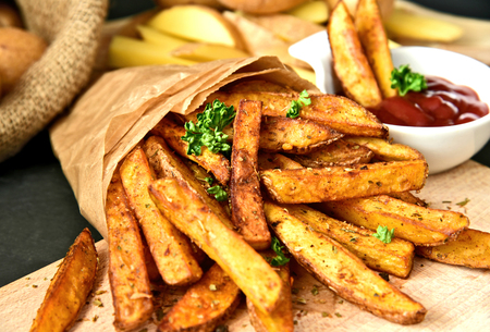 Homemade Crispy Seasoned French Fries.French fries with spicy seasoning in brown paper bag on wooden broad. Reklamní fotografie