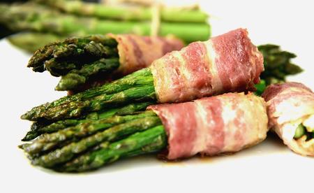 Bacon Wrapped Asparagus Bundles on white dish.spring vegetable season with BBQ menu.