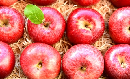A lot of fresh Red Gala apples with green leaf on Straw or wood wool shavings packaging in the supermarket. Stok Fotoğraf