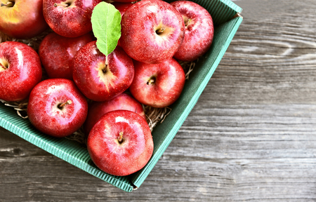 A lot of fresh Royal Red Gala apples and green leaf in paper box on wooden background.