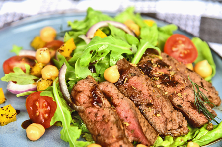 Steak salad with honey soy sauce on blue dish.Beef salad with arugula and chickpeas.