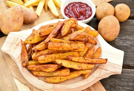Homemade Crispy Seasoned French Fries.French fries with spicy seasoning on wooden plate on wooden broad.
