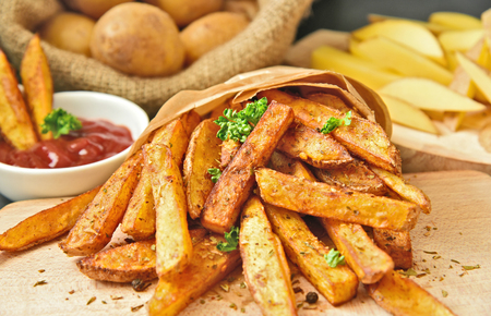 Homemade Crispy Seasoned French Fries.French fries with spicy seasoning in brown paper bag on wooden broad. Stok Fotoğraf