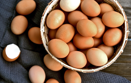 Healthy and benefits of chicken egg.Many chicken eggs in basket on wooden background.