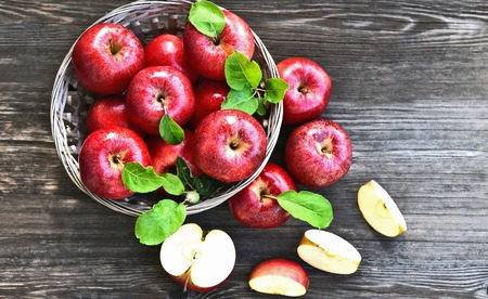 a lot of Red apples or Gala apples with fresh leaf  on wooden background.
