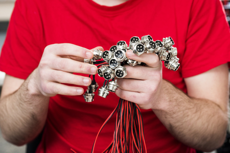 metal electric four pin connectors in male hands Stock Photo