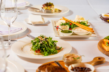 cheese sliced and salads on a beautiful white banquet table