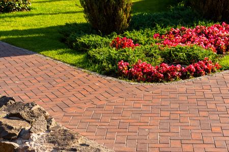 Camino de losa roja junto a flores en el diseño del paisaje