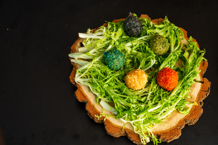 Cheese balls on a wooden plate with greens on a black background