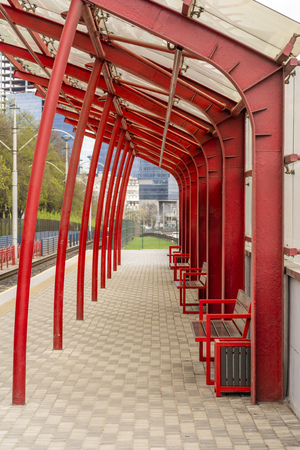metal structures with a glass roof and benches at a public transport stop