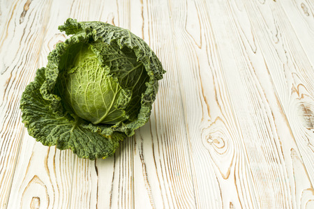 Fresh Savoy cabbage from the garden on a wooden table, ingredients for cooking Stock Photo