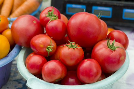 red tomatoes in a plastic plate on the counter for sale on the market