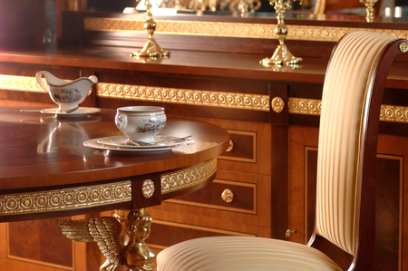 tea-drinking at the table on the armchair and furniture made of wood with bronze inserts and stucco molding