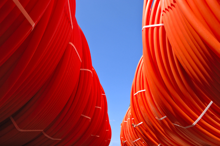 plastic pipes stacked in rolls on the street on the sky background
