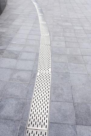 Gutter cover or sewer drain on roadside. street rain gutter Imagens - 110100472