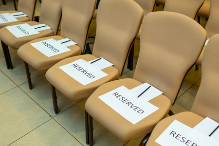 conference chairs reserved for guests with notebooks and pencils for notes Standard-Bild
