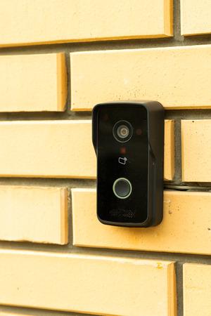 campanello di strada con una videocamera su un muro di mattoni