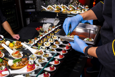 gloved hands putting food at the banquet Banco de Imagens