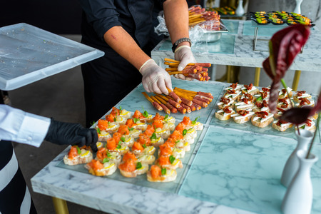 A waiter in gloves at a banquet prepares a table for guests.