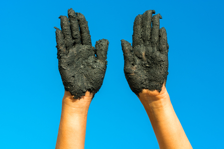 medical mud on female hands against the blue sky Stock Photo