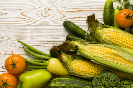 A variety of fresh vegetables from the garden, corn cobs with tomatoes and cucumbers and cabbage, sweet peppers and zucchini. Top view on a white wooden table. with free space for text 스톡 콘텐츠