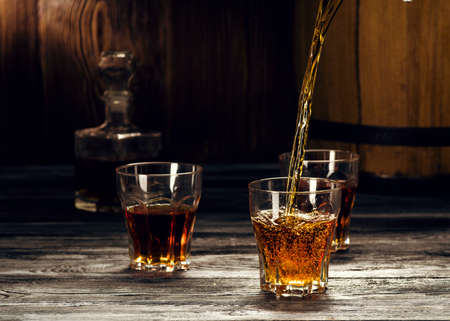 Cognac in glasses, in a wooden barrel cellar, strong refined alcoholic beverage Zdjęcie Seryjne
